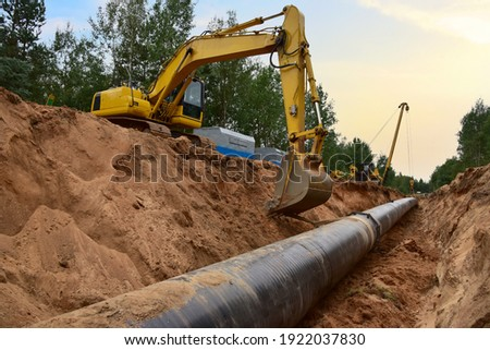 Natural Gas Pipeline Construction. Gas and Crude oil transmission in pipe from gas storage and plant development to facility.  Excavator and pipelayer during building of transit petrochemical pipes