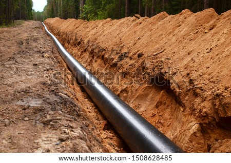Natural gas pipeline construction work. A dug trench in the ground for the installation and installation of industrial gas and oil pipes. Underground work project