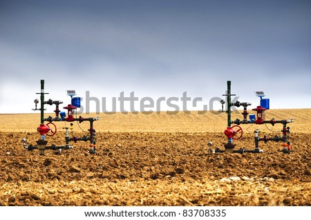 Natural gas wellheads in a plowed cornfield.