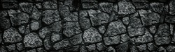 Natural granite stone wall wide texture. Dark rock masonry widescreen gloomy gothic background