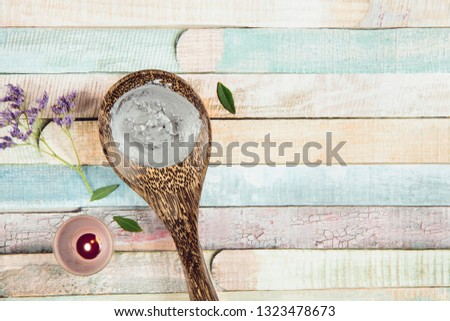 Natural gray mud mask cream on wooden spoon with candle burning and flower branch as decoration on colorful wooden background. Flat lay view, copy space, copy space.