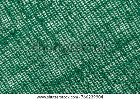 Natural green burlap for Christmas decorating. Green jute texture on green background. St. Patrick's day background #766239904