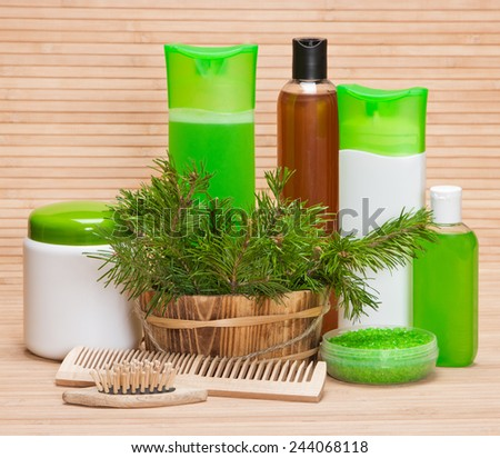 Natural hair care cosmetics and accessories: wooden basket filled with pine branches, sea salt, shampoo, conditioner, balm, mask, wooden combs
