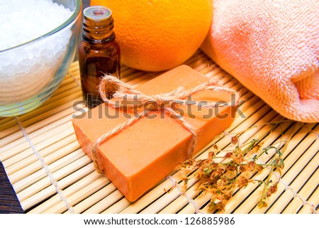 Natural handmade soap, essential oil, dried herbs, bath salt, orange and towel on bamboo mat. Spa concept.