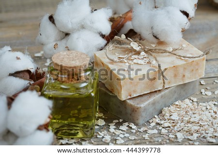 Natural handmade soap, oat flakes, aromatic oil and cotton branch on wooden background. Spa concept. #444399778