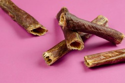 Natural healthy treats for dogs 100% premium quality. Dried beef esophagus, buffalo giblets on a pink background. Dehydrated meat. Dog food, Chew treats, Pet supplies. Close-up, selective focus.