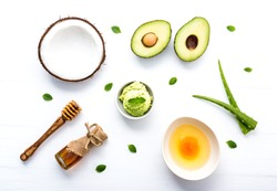 Natural herbal skin care products, top view ingredients coconut, mint, aloe vera, avocado,egg,honey on table concept of the best all natural face moisturizer. Facial treatment preparation background.