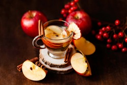 Natural homemade autumn hot drink: spicy beverage made from fresh and dried dehydrated apples with cinnamon and honey. Fresh fruits to illustrate ingredients. Can also be warm punch or mulled wine.