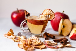 Natural homemade autumn hot drink: spicy beverage made from fresh and dry dehydrated apple chips with cinnamon and honey. Fresh fruits. Can also be warm punch or mulled wine