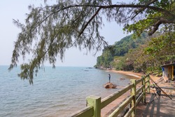 Natural image of tropical sea side with unknown man standing on the rock in water and fishing rods on the shore at Aow Yang bay beach in Chanthaburi province east of Thailand