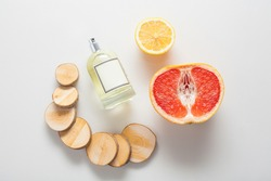 Natural ingredients for a woody citrus fragrance, a bottle of oil or perfume on a background of grapefruit, lemon and wood. The concept of perfumes and aromatherapy, body care, natural oils.