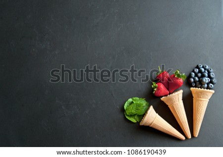 Natural ingredients spilling out of an icecream cones including strawberry, mint and blueberry flavors #1086190439