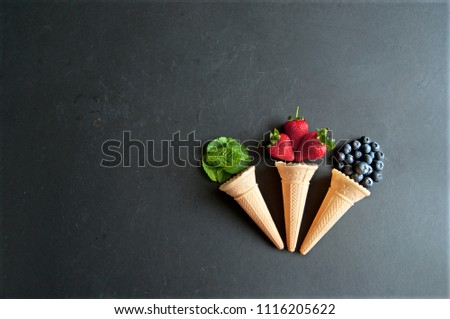 Natural ingredients spilling out of an icecream cones including strawberry, mint and blueberry flavors #1116205622