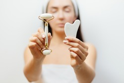 Natural Jade Face Lifting Gouache Scraper Massager. Beautiful Woman Using face roller and Gua Sha scraper over skin. beauty face skin care at home.