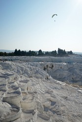 Natural landscape and Thermal pools of Pamukkale (Cotton castle) mineral-rich thermal waters flowing down white travertine terraces on a nearby hillside formed by ancient hot springs- Denizli, Turkey