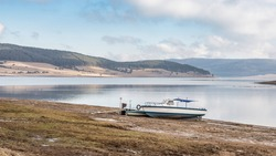 Natural landscape. Blue fisherman boat on the coast, beautiful white clouds on blue sky and blurry reflections on the water surface of Batak Dam, lake in the Rhodope Mountains, Bulgaria.
