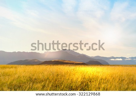 Natural landscape of summer field and high mountain