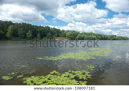Natural landscape with river, trees, blue sky and many clouds