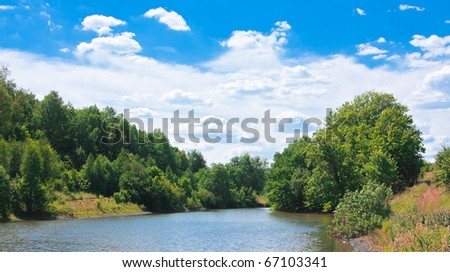 Natural landscape with sky, forest and pond