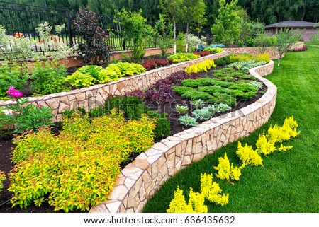 Natural landscaping with decorative stone in house backyard. Beautiful landscaping with flowerbed in summer. Landscape design of the home garden.