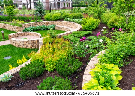 Natural landscaping with decorative stone in nice backyard. Beautiful landscaping with flowerbed in summer. Landscaped flower garden in luxury home yard.