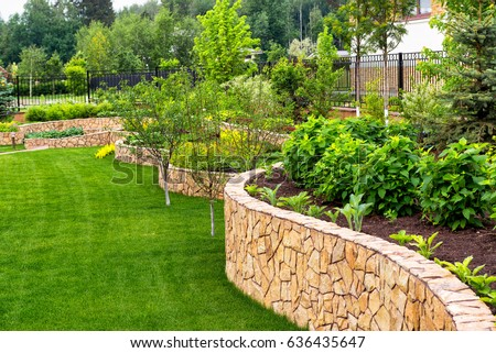 Natural landscaping with decorative stone in residential backyard. Beautiful landscaping with flowerbed and green lawn in summer. Landscape design of the nice home garden.