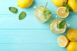 Natural lemonade with mint on light blue wooden table, flat lay and space for text. Summer refreshing drink