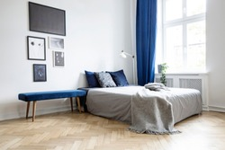 Natural light coming through a large window into a white and navy blue bedroom interior with cozy bed and hardwood floor