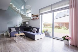 Natural light coming through big glass door to a monochromatic, open space living room interior with a modern sofa on hardwood floor