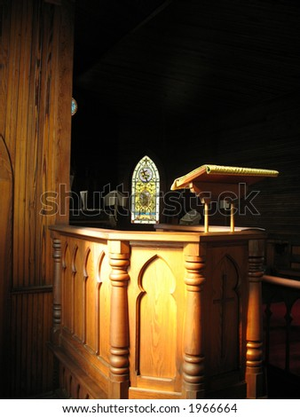 natural light of very old stained glass windows falls across the antique lectern in this historic  little church, built in early 1800s