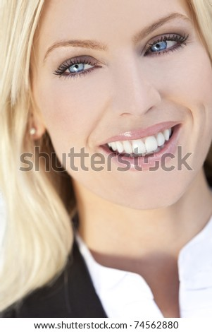 Natural light portrait of a beautiful smiling blond woman with blue eyes
