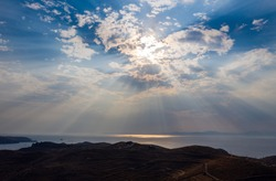 Natural light rays and blue cloudy sky over sea in twilight. Sunbeams reflections on calm sea water. Kea Tzia island, Aegean sea, Greece