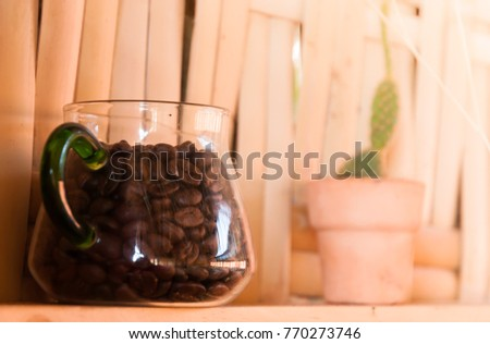 Natural lighting and shadow of blur coffee beans in a glass jug on bamboo wall in coffee shop in Chaing mai,Thailand. coffee beans background with copy space. cafe concept. #770273746