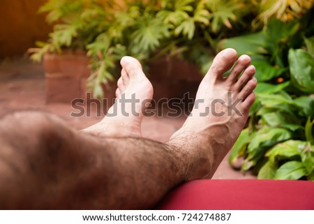 Shutterstock Natural lighting and shadow of blur man's hairy legs on day bed beside swimming pool in resort. hairy legs background with copy space. sunbathing and chilling at swimming pool in summer concept.
