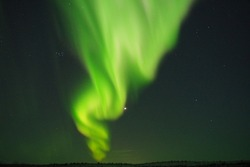 Natural looking green aurora borealis (northen lights) with Venus and stars in the border of Finland and Norway