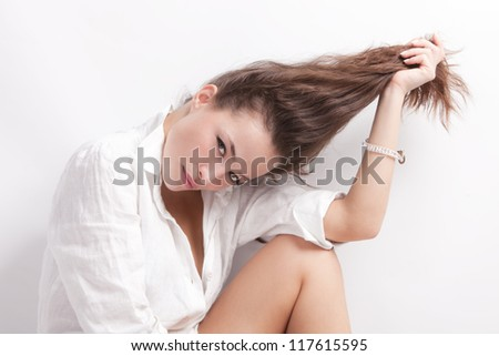 natural looking young woman portrait holding her long hair in one hand studio shot