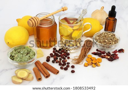 Natural medicinal herbal remedy for cold & flu virus with hot drink with fresh ginger, lemon, honey, cinnamon. echinacea, hawthorn berries, ginseng & eucalyptus essential oil. Immune boosting. Stockfoto ©