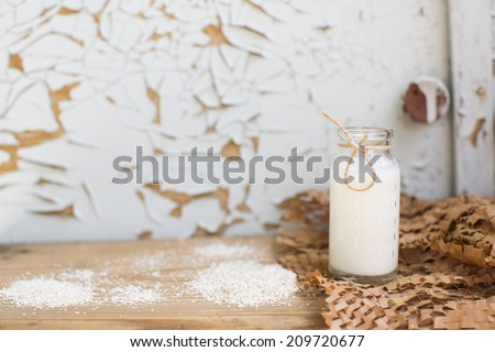 Natural milk bottle standing on a wooden table on a background of old furniture. Still-life with natural healthful food. Dairy