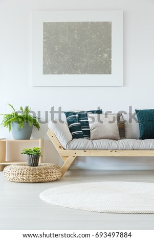 Natural minimalist home decor with white wall, mock-up painting, plants, wooden sofa and decorative pillows #693497884