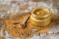 Natural mustard in a jar. Grains of mustard. Homemade mustard. Organic mustard. Selective focus. Macro.