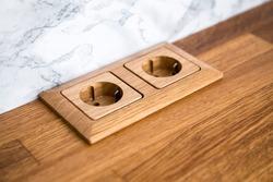 Natural oak wood socket built in natural wood kitchen counter.