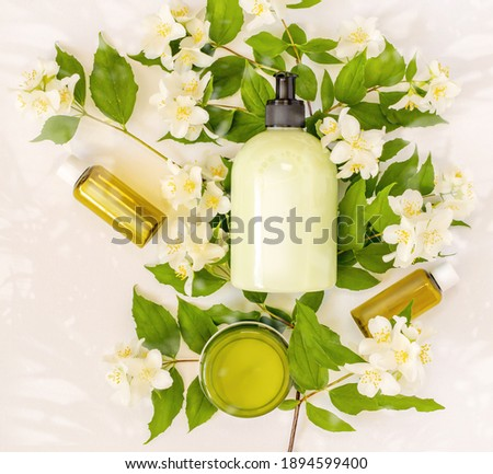 Natural organic cosmetic packaging plastic mock up with leaves and flowers. Beauty mock-up bottles for branding and label on a blooming apple branch with sun glare on white background. Flat lay Foto d'archivio ©