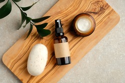 Natural organic cosmetics set top view. Homemade soap, jar of moisturizer cream, body spray in amber glass bottle, green leaf on wooden board. SPA bathroom beauty product design, branding.