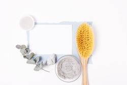 Natural organic cosmetics template with blank card in center among clay mask, wooden brush and eucalyptus sprig on white background, flat lay