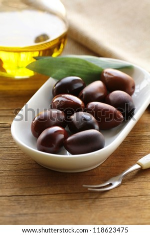 natural organic olives in a white bowl, a bottle of oil in the background