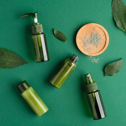 Natural organic SPA cosmetic products set with green leaves. Top view herbal skincare beauty products on green background.