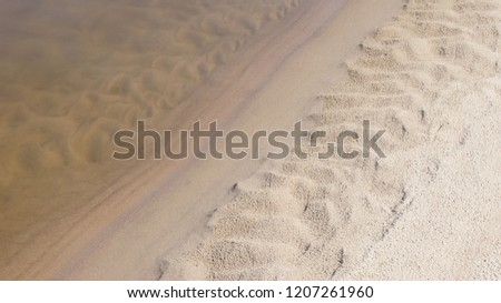 Natural patterns in the sand formed on the water and land border line. Interesting sand formation shapes seen over and under water. Detail of the beach on Vistula River. #1207261960