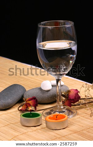 Natural pebbles, candle, glass and dried rose petals on the rattan background. Suitable for spa, relaxation and romance setting