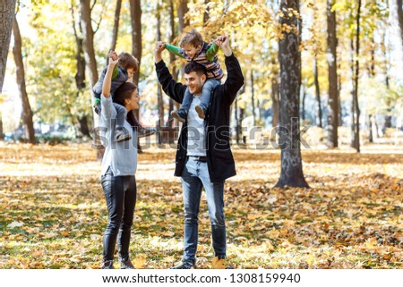 Natural pictures of a happy family of four having fun outsiade on a sunny autumn day. Togetherness and happiness concept