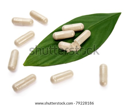 Natural pills and a green leaf - stock photo